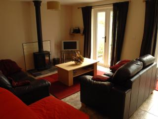 Lounge with log burner, tv/dvd and pair of french windows leading into enclosed garden.