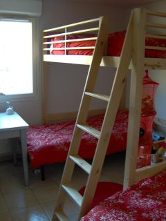 The second bedroom has two single beds, an upper-bunk bed and a large built-in wardrobe