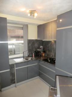Modern kitchen with coffee machine, dishwasher, microwave, gashob