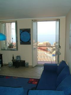 Living room with french doors open onto balcony/sea view over Pizzo