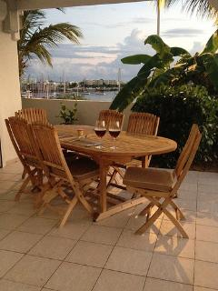 Outside teak dining table- situated in overhead roof covered area with 3 ceiling fans for a breeze.