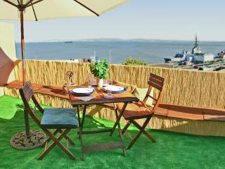 Terraza con vistas al estuario del Tajo y muebles de jardín, incluyendo varios cojines