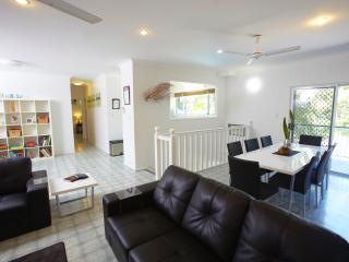 Lounge, dining, stairs. sliding doors open onto balcony with outdoor seating area and BBQ