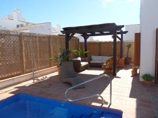 Shaded pergola area with sofas