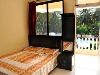 Bedroom facing poolside with airconditioner and one double bed
