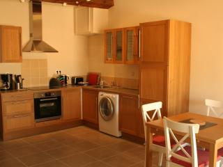 Fitted kitchen and open plan dining area. The dining table extends to comfortably seat six people.