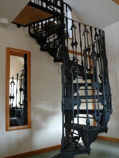 spiral staircase leading up to gallery bedroom