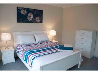 Large main bedroom with queen size bed, all linen supplied and views over the garden and bay