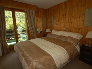 Main bed is kingsize with fitted wardrobes; doors lead to rear balcony