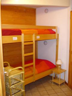 Bunk area set back in separate area with storage cupboard and drawers