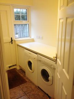 The utility room off the kitchen which contains tumble dryer, washing machine and oil burner.