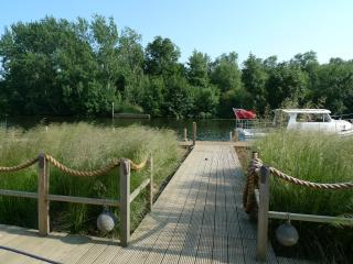 Large deck & lawned garden by unfenced river. Hire canoes, day boat, or cruiser at adjacent boat