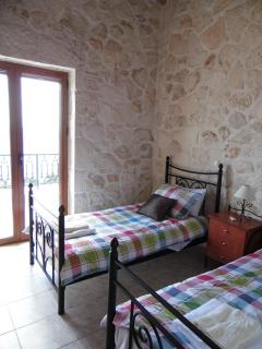 Twin bedroom with double doors to balcony looking out over the Ionian Sea