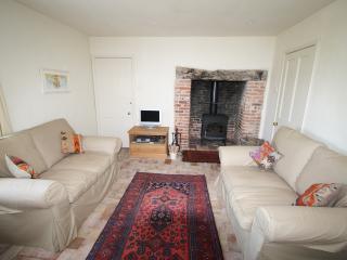Sitting room with inglenook, cosy woodburner, Suffolk brick floor with rugs