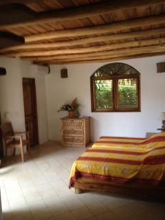 2 person bedroom in bungalow with door to bathroom in left corner