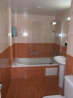 Fully tiled bathroom with bath and overhead shower