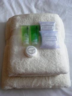 Fresh white bath sheets and towels with complimentary toiletries