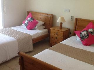 Attractive twin bedroom with fitted wardrobes and large patio door out to garden and pool.
