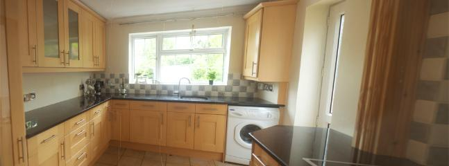 Fully fitted kitchen overlooking back garden and lake, back door leads out to garden