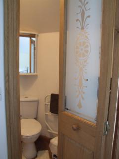 En suite shower room with oak part-glazed folding door.