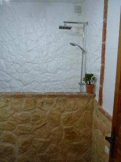 Stoned walled bathroom with large walk-in twin-headed shower & foot wash