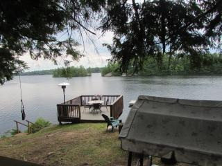 View of deck and swinging chair looking from back deck on cottage