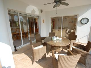 Beautiful south facing balcony overlooking  pool with quality dining table chairs and ceiling fan