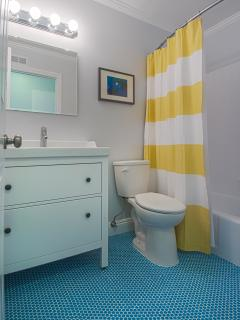 Upstairs full bath with sparkling white tub and blue penny tile floors