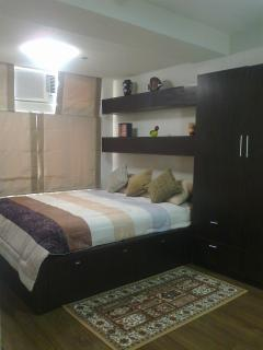 Queen size bed with linens, air conditioning unit