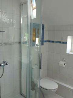 A lovely shower room bathed in natural light is home to an original gold leaf on acrylic painting
