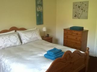 Main bedroom boasts lovely king size pine bed.