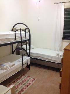 camera con letto a castello, letto singolo, ventilarore a tetto e cassettiera