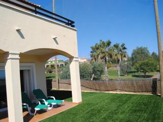 Jardin privado con porche, muebles de jardín y se aprecia la terraza solarium arriba.