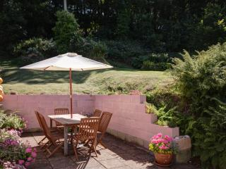 This pretty patio is a sun trap ideal for BBQ's.Steps lead up to a grassy sloping garden.