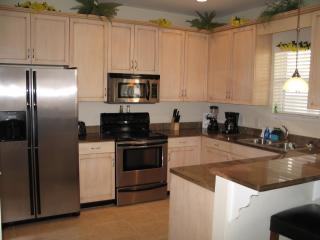Fully equipped kitchen with granite counter tops, stainless full sized appliances, breakfast bar