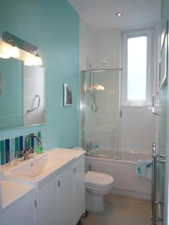 Bathroom with small bath and electric shower
