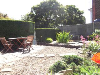 Gated garden.  Outdoor furniture including table, chairs, parasol and bbq