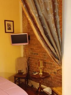 Bedroom with exposed brick, flat screen television.