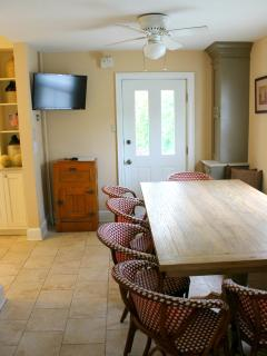 large farm table for in-kitchen dining with view of TV