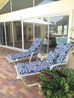 Lounge chairs on patio. 20' wide sliding doors lead into the living room.