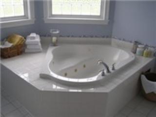 Jacuzzi para dos además de una azulejo de la ducha y dos lavabos.