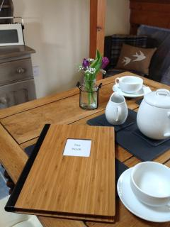 Dining table in The Nook, with welcome pack.
