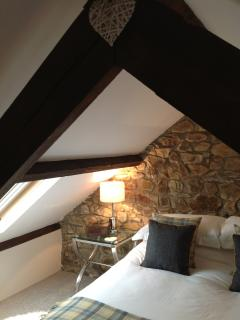 Lovely old beams and stone wall in the bedroom