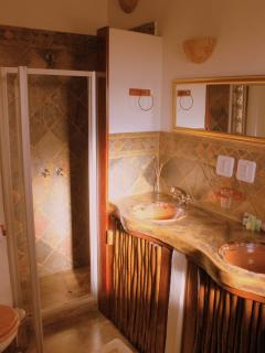 En suite bathrooms with toilet, double sink, bath and separate shower. In African style.