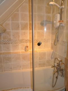 Natural stone tiles, Edwardian telephone brass taps, separate showers above, full length baths