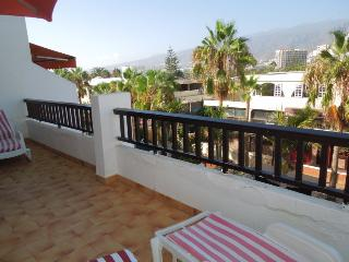 Large terrace with a bit sea-view on the left side and sunbeds