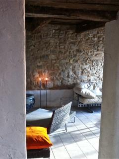 Ground floor living room: natural stone walls, italian stone floor and design-icon furniture