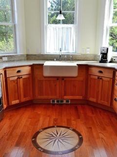Bay-shaped, bright kitchen has lots of granite counters, a farm sink, and gas appliances