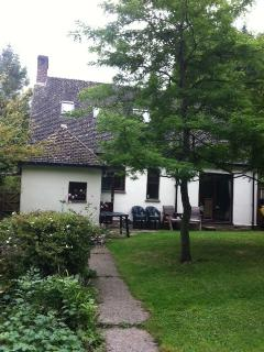 Back view of cottage, there is a lovely patio area for people to sit.