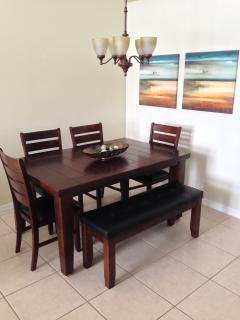 The formal dining area has a large wood table with six leather chairs.